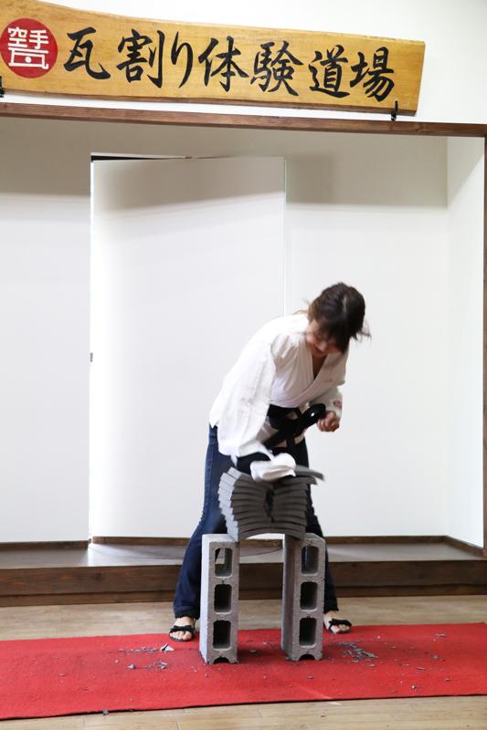 瓦を真っ二つに割る女性